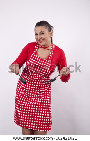 Young attractive housewife with kitchen tools.