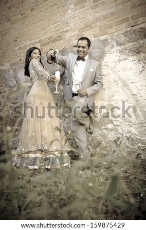 Young attractive indian couple enjoying a moment in garden with champagne glasses  - stock photo