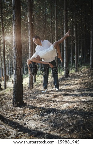 Young attractive indian couple wearing white dancing together in a forest of trees  - stock photo