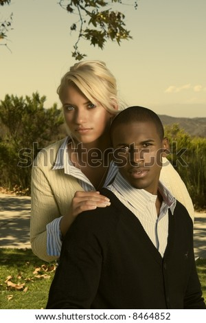 young attractive interracial couple in a park - stock photo