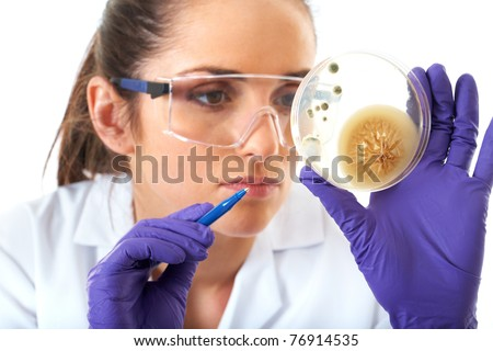 young attractive laboratory assistant check petri dish with agar and bacterium on it, isolated on white - stock photo