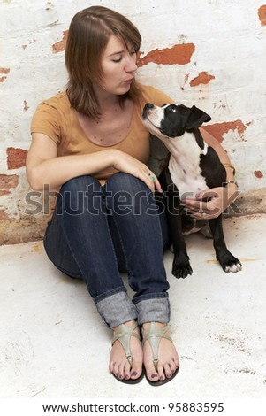 Young attractive lady and dog interact - stock photo