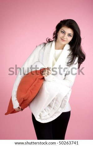 Young attractive lady going to sleep with pillow and quilt over pink background - stock photo