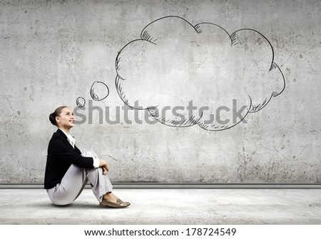 Young attractive lady sitting on floor of empty room - stock photo