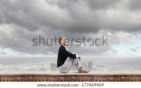 Young attractive lady sitting on top of building
