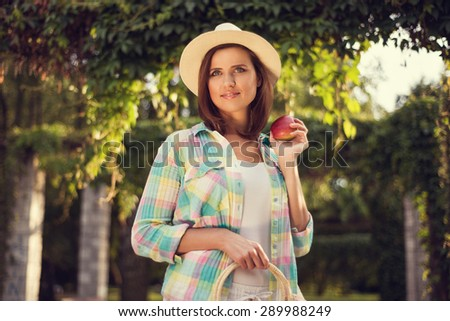 Young attractive lady with apple and bag