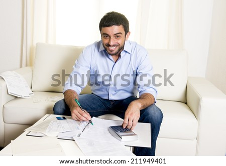 young attractive latin american business man at home sitting on sofa with credit card and calculator accounting costs, charges, taxes and mortgage for paying bills looking happy and relaxed  - stock photo