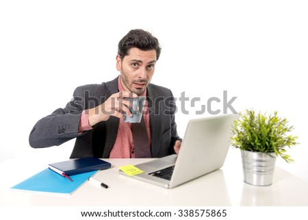 young attractive Latin businessman in suit and tie working at office computer desk drinking cup of coffee typing on the laptop in success on business concept - stock photo