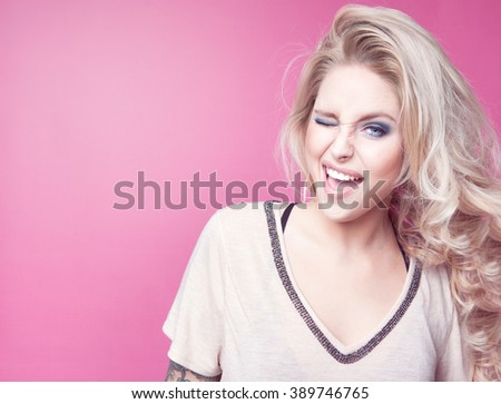 Young attractive laughing winking blonde happy woman expressive portrait beauty concept - stock photo