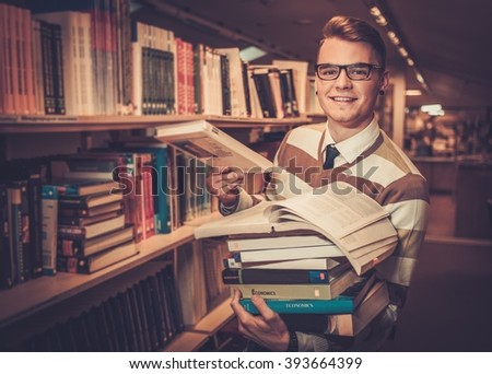 Young attractive librarian holding a pile of books in the university library. - stock photo