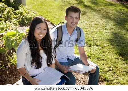 Young, attractive male and female students outside studying - stock photo
