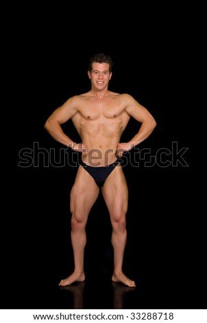 Young attractive male body builder, demonstrating contest pose. Studio shot, black background. - stock photo