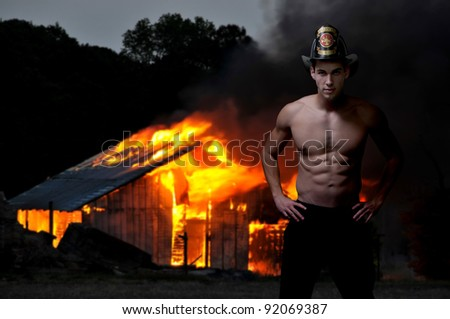 Young attractive male firefighter at a fire - stock photo