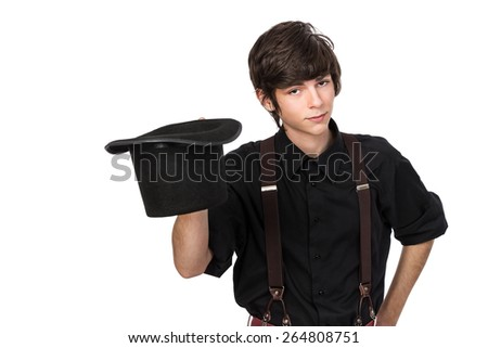 Young attractive male in a black shirt and jeans suspenders, holding a black hat in a hat off salute, with a confident and inquisitive expression on his face, isolated on white - stock photo