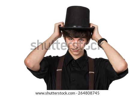 Young attractive male in a black shirt and jeans suspenders, putting on his head a black top hat, with a confident and smiling expression on his face, isolated on white - stock photo