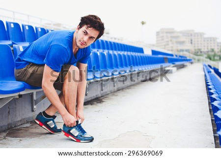 Young attractive male model in blue shirt  tying laces on his running shoes and looking at field before run on a stadium stands after workout perspective view. Copy space - stock photo