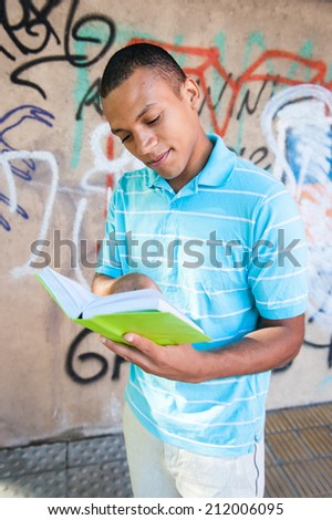 Young attractive male reading a book. Outdoors. - stock photo