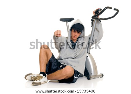 Young attractive male teenager in front of fitness bike, bicycle. Studio shot, white background. - stock photo