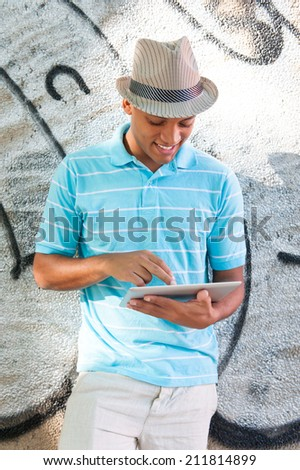 Young attractive male using tablet pc. Outdoors. - stock photo