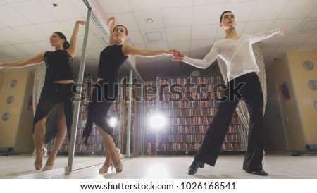 Young attractive man and woman dancing and rehearsing Latin American dance in costumes in the Studio, focus reflection in the mirroron and legs