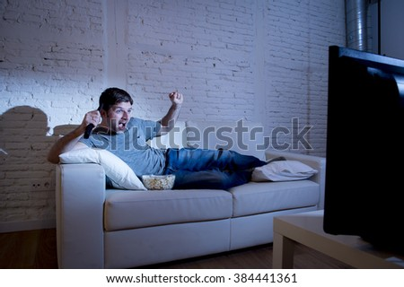 young attractive man at home lying on couch at living room watching sport match on tv holding remote control celebrating goal or victory screaming happy and excited - stock photo
