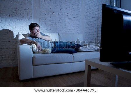 young attractive man at home lying on couch at living room watching tv  eating popcorn bowl looking surprised and in shock maybe with a horror film or disaster breaking news