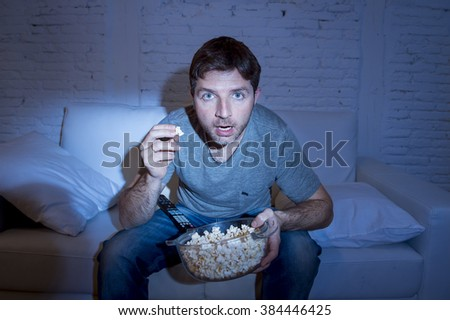 young attractive man at home lying on couch at living room watching tv holding popcorn bowl eating and looking mesmerized and intense concentration in television addict concept - stock photo