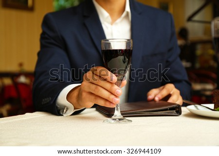 Young attractive man at the restaurant. Focus on wine glass - stock photo