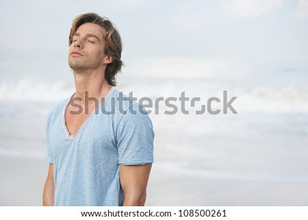 Young attractive man breathing fresh air while on the beach, with the sea in the background. - stock photo