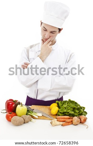 Young attractive man, chef thinking what to cook. Ingredients on table. Studio shot. White background. - stock photo