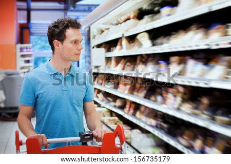 young attractive man choosing food in the supermarket - stock photo