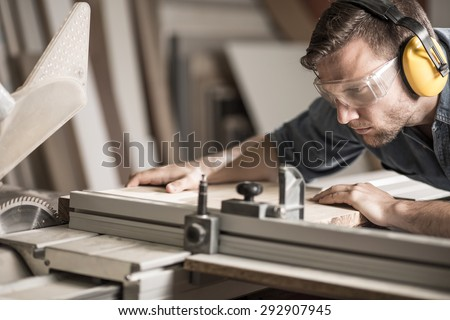 Young attractive man doing woodwork in carpentry - stock photo
