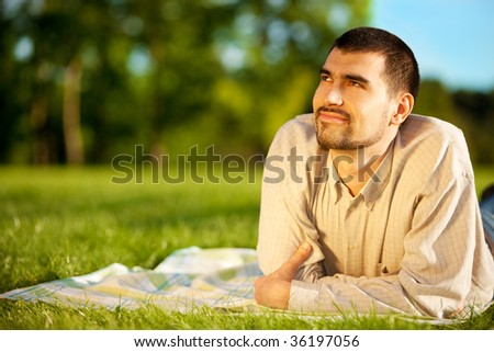 Young attractive man dreaming on a meadow - stock photo
