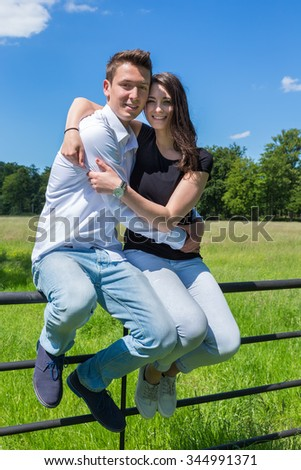 Young attractive man embracing woman in nature on sunny day - stock photo