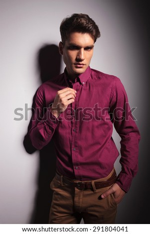 Young attractive man holding his hand in pocket while fixing his collar.