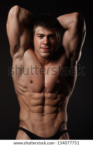 Young attractive man in a black bathing suit bodybuilder with relief muscles - stock photo