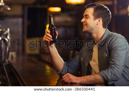 Young attractive man in casual clothes is smiling and holding a bottle of beer while sitting at bar counter in pub - stock photo