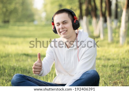 Young attractive man in headphones outdoor - stock photo