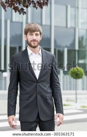 Young attractive man in suit in front of his company - stock photo