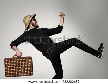 Young, attractive man  in sunglasses wtih  suitcase ready to travel as tourist on gray background. shot in profile - a man walks on vacation strides - stock photo