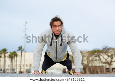 Young attractive man in sweatshirt doing push ups outdoors, fitness and sport lifestyle concept - stock photo