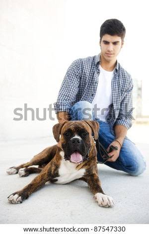 Young attractive man in urban background with his dog - stock photo