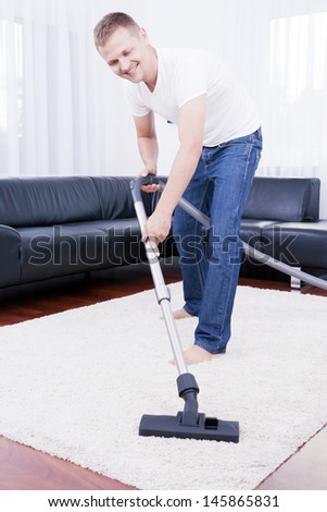 Young attractive man is cleaning vacuum on carpet. - stock photo