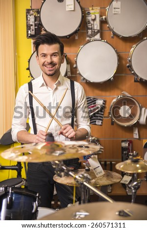 Young attractive man is playing the drums in the music store. - stock photo