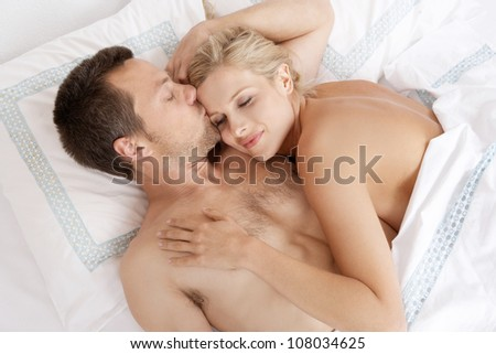 Young attractive man kissing woman's forehead in bed. - stock photo
