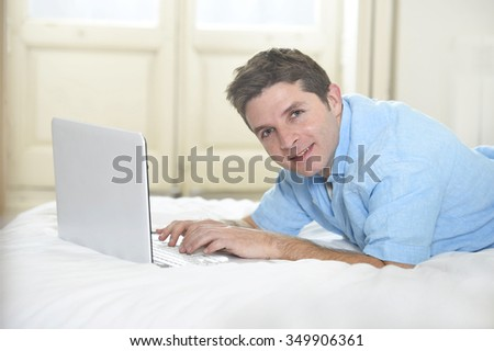 young attractive man lying on bed enjoying social networking using  computer laptop at home wireless connected to internet in technology and modern lifestyle concept