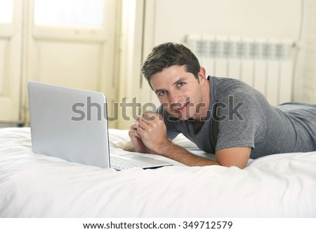 young attractive man lying on bed or couch enjoying social networking using  computer laptop at home wireless connected to internet in technology and modern lifestyle concept