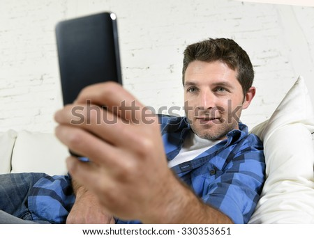 young attractive man lying relaxed at home couch texting and surfing on internet in his mobile phone looking happy , satisfied and confident  in technology concept - stock photo
