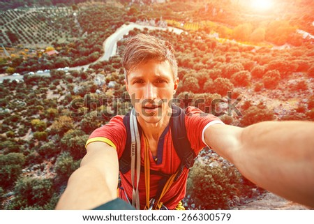 young attractive man make selfie from the cliff on the gardens background - stock photo