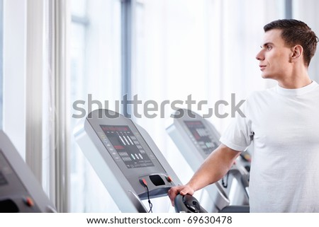 Young attractive man on a treadmill